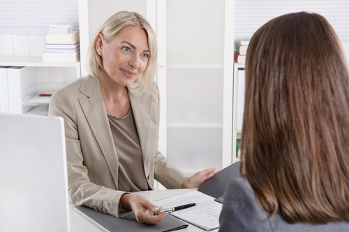 Mature businesswoman in a job interview with a young woman.